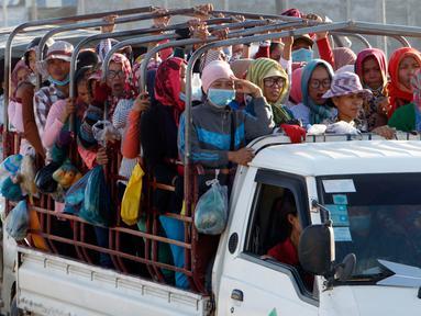 Para pekerja menaiki mobil bak terbuka sebagai transportasi harian mereka pulang ke rumah dari tempat kerja di sebuah pabrik di dekat desa Trapang Anchanh, di luar Phnom Penh, Kamboja (27/10). (AP Photo/Heng Sinith)