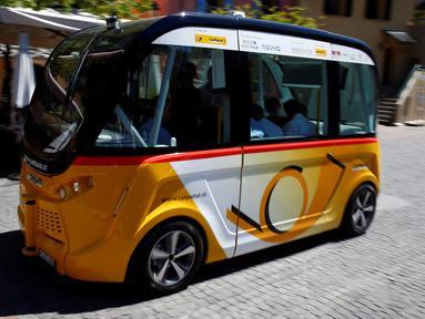 Sebuah angkutan umum tanpa kemudi dan sopir melintasi jalanan Sion, Swiss, Kamis (23/6). Angkutan umum listrik pertama buatan PostAuto Schweiz ini memiliki 11 kursi penumpang dengan kecepatan maksimal 20 km per jam. (REUTERS/Ruben Sprich)