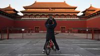 Seorang anak laki-laki mengambil foto di luar Kota Terlarang yang ditutup di Beijing pada Selasa (4/2/2020). Mencegah korban virus corona bertambah, China menutup  banyak destinasi wisata termasuk Kota Terlarang yang ditutup untuk kunjungan wisatawan sejak 24 Januari 2020 lalu. (GREG BAKER/AFP)