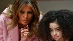 Melania Trump mengunjungi anak-anak yang dirawat rumah sakit National Institutes of Health untuk merayakan Hari Valentine, Maryland, Kamis (14/2). Nuansa valentine sangat terasa dalam busana serba merah muda yang dipakai Melania saat itu (MANDEL NGAN/AFP)
