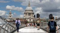 Orang-orang berjalan di Jembatan Milenium dengan latar pemandangan Katedral St. Paul di London, Inggris, 1 Agustus 2020. Pemerintah Inggris pada Jumat (31/7) mengumumkan penundaan pelonggaran beberapa langkah pembatasan menyusul jumlah infeksi virus corona yang meningkat. (Xinhua/Han Yan)