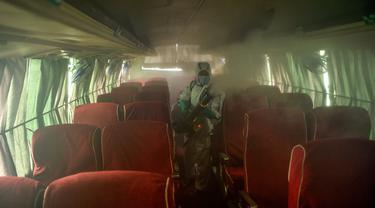 Seorang pekerja yang mengenakan Alat Pelindung Diri (APD) menyemprotkan disinfektan pada bus di Kathmandu, Kamis (17/9/2020). Pemerintah Nepal melonggarkan pembatasan yang diberlakukan sebagai tindakan pencegahan terhadap virus corona pada transportasi umum jarak jauh. (PRAKASH MATHEMA/AFP)
