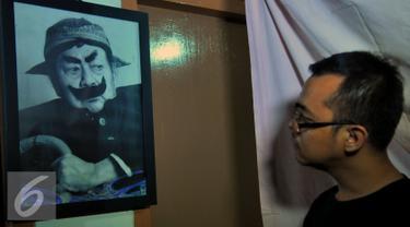 Seorang kerabat memandangi lukisan wajah Almarhum Pak Raden atau Suyadi di rumah duka Petamburan III, Jakarta (30/10/2015). Pak Raden menghembuskan napas terakhirnya di Rumah Sakit Pelni. (Liputan6.com/Faisal R Syam)