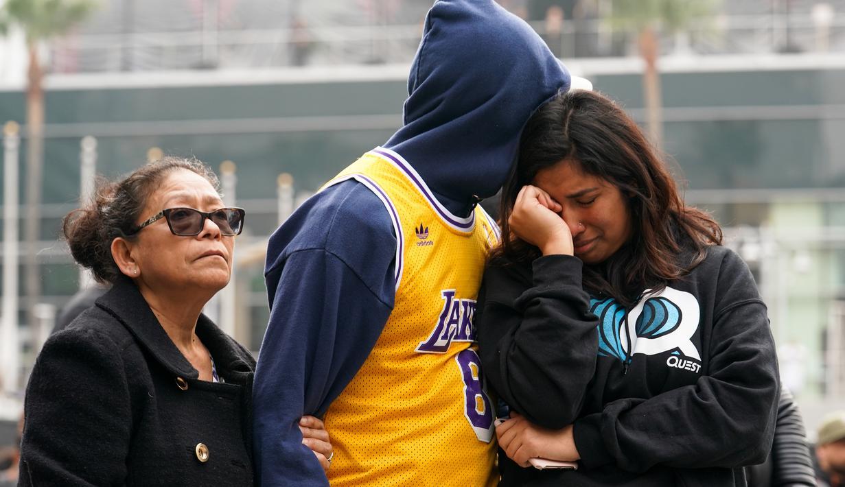 Fans LA Lakers tampak sedih usai Kobe Bryant meninggal dunia di Staples Center, Minggu (26/1/2020). Legenda basket NBA itu wafat dalam kecelakaan helikopter di Calabasas, California. (AFP/Rachel Luna)