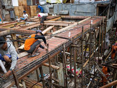 Para pekerja menyelesaikan pembangunan rumah panggung di dekat bantaran Kali Ciliwung, Kampung Melayu, Jakarta, Rabu (7/4/2021). Pemerintah Provinsi DKI Jakarta melakukan renovasi terhadap 40 hunian warga Kampung Melayu menjadi rumah panggung. (Liputan6.com/Faizal Fanani)