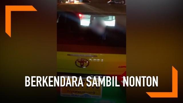 Seorang sopir taksi berkendara sambil menonton film dewasa di Thailand. Tindakan sopir taksi ini diketahui oleh pengendara lain yang geram melihat cara sopir taksi berkendara.