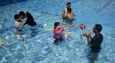 Anak-anak Palestina yang menderita autisme berpartisipasi dalam sesi terapi renang di Beit Lahia di Jalur Gaza utara  (5/8/2019). (AFP Photo/Mohammed Abed)
