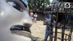 Perajin menyelesaikan pembuatan ondel-ondel di Kawasan Perkampungan Budaya Betawi, Setu Babakan, Jagakarsa, Jakarta Selatan, Selasa (28/7/2020). Ondel-ondel tersebut dijual mulai dari Rp 35 ribu hingga Rp hingga 8 juta. (merdeka.com/Dwi Narwoko)