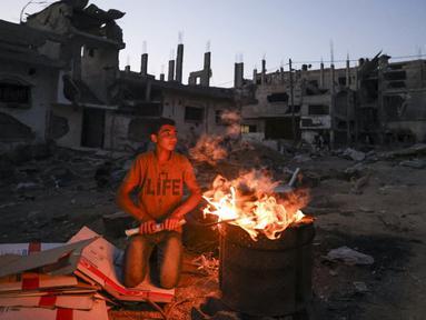 Seorang pemuda Palestina bersiap untuk memasak jagung dekat bangunan yang hancur selama konflik antara Hamas dan Israel pada Mei 2021 di Beit Hanun, Jalur Gaza, Senin (7/6/2021). Hamas dan Israel gencatan senjata setelah perang selama 11 hari. (MAHMUD HAMS/AFP)