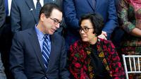 Sekretaris Menteri Keuangan Steven Mnuchin berbicara dengan Menteri Keuangan Sri Mulyani Indrawati saat akan sesi foto ketika rapat World Bank/IMF Spring di Washington, (22/4). (AP Photo/Jose Luis Magana)