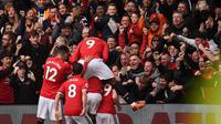 Ilustrasi para pemain Manchester United (MU) saat merayakan gol di hadapan pendukungnya. (Oli SCARFF / AFP)