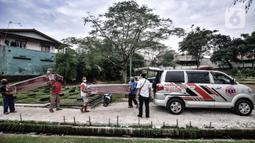 Pekerja membawa peti jenazah yang selesai dibuat untuk dipindahkan ke ambulans di TPU Pondok Kelapa, Jakarta, Selasa (13/7/2021). Berbanding terbalik pada masa sebelum Lebaran, dalam sehari pekerja hanya memproduksi 10-15 peti jenazah. (merdeka.com/Iqbal S Nugroho)
