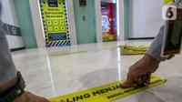 Pekerja memasang stiker saling menjaga jarak di depan lift Lippo Mall Puri, Jakarta, Rabu (3/6/2020). Lippo Malls Indonesia (LMI) menyiapkan prosedur dengan menerapkan protokol kesehatan menuju new normal di seluruh mal di 34 kota besar di Indonesia. (Liputan6.com/Fery Pradolo)