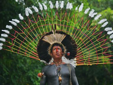 Seorang pria bernama Txoutlaka dari suku Fulni-o berpose untuk difoto di Rio de Janeiro, Brasil (14/4). Sejumlah orang dari suku asli Brasil berkumpul untuk merayakan Indian Day di Rio de Janeiro. (AFP/Carl De Souza)