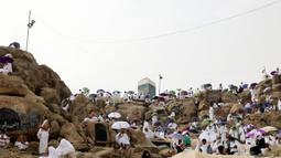 Jemaah haji berkumpul di sekitar Jabal al-Rahma (Gunung Rahmat) saat menunaikan prosesi wukuf di Padang Arafah, tenggara Kota Suci Mekah, Arab Saudi, Senin (19/7/2021). Wukuf di Padang Arafah dua tahun terakhir berada dalam pembatasan karena pandemi corona virus COVID-19. (FAYEZ NURELDINE/AFP)