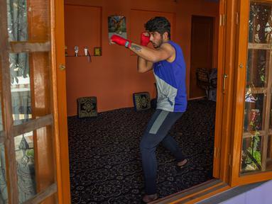 Petinju Kashmir, Eyed Akeel Khan melakukan latihan di dalam rumahnya di Srinagar, Kashmir yang dikuasai India pada 23 April 2020. Seperti atlet yang lain, Khan harus menjalani latihan di rumah namun, lockdown bagi 7 juta penduduk Kashmir bukan hal yang baru. (AP Photo/Dar Yasin)