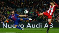 Penyerang Barcelona, Luis Suarez berebut bola dengan pemain Girona, Juanpe Ramirez saat bertanding pada La Liga Spanyol di stadion Camp Nou (25/2). Barcelona menang telak 6-1 atas Girona. (AP Photo/Manu Fernandez)