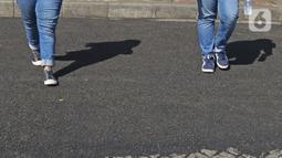 Pengunjung melewati contoh aspal lintasan Formula E di Monas, Jakarta, Minggu (23/2/2020). Aspal untuk sirkuit Formula E di uji coba di Monas, lokasi pengaspalan itu berada di Monas bagian timur. Pengaspalan dilakukan dengan dua metode, sandsheet dan geotextile. (Liputan6.com/Herman Zakharia)