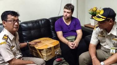 Petugas BKSD Bali menunjukkan pelaku warga negara Rusia Andrei Zhestkov (tengah) yang menyelundupkan orangutan berusia dua tahun di keranjang rotan, di bandara internasional Bali (23/3). Orang utan itu rencananya akan dibawa dari Bali ke Rusia. (AFP Photo/Badan Konservasi Sumber Daya Alam Bali)
