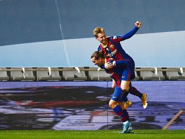 Gelandang Barcelona, Frenkie de Jong, melakukan selebrasi bersama Antoine Griezmann usai mencetak gol ke gawang Real Sociedad pada laga semifinal Piala Super Spanyol di Stadion Nuevo Arcangel, Rabu (13/1/2021). Barcelona menang adu penalti dengan skor 3-2. (AP/Jose Breton)