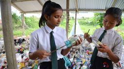 """Siswa India memasukkan kantong plastik ke dalam botol untuk membuat """"batu bata ramah lingkungan"""" di sekolah Forum Akshar di desa Pamohi, Guwahati, 20 Mei 2019. 110 murid sekolah ini harus membawa 20 item sampah plastik per minggu yang dikumpulkan dari rumah atau area sekitar mereka. (Biju BORO/AFP)"""