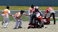 Petugas membantu pembalap Ducati, Andrea Dovizioso dan Jorge Lorenzo setelah mengalami tabrakan beruntun pada balapan MotoGP Spanyol 2018 di Sirkuit Jerez, Minggu (6/5). Mereka mengalami crash delapan lap sebelum bubaran.  (AFP/JAVIER SORIANO)