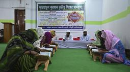 Anggota komunitas transgender belajar membaca Alquran di dalam Madrasah Dawatul Islam Tritio Linger untuk jenis kelamin ketiga, di Dhaka, Bangladesh, Selasa (17/11/2020). Pendirian madrasah ini dianggap salah satu upaya Bangladesh untuk membuat hidup kaum LGBT lebih mudah. (Munir Uz zaman/AFP)