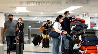 Wisatawan keluar dari pintu kedatangan Internasional di Bandara Miami, Florida, Senin (20/9/2021). Amerika Serikat akan mencabut larangan perjalanan covid-19 pada semua penumpang udara yang sudah divaksin lengkap dan menjalani tes serta pelacakan kontak pada November. (Joe Raedle/Getty Images/AFP)