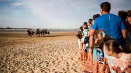 Sejumlah joki memacu kuda mereka pada lomba pacuan kuda di sepanjang pantai di Sanlucar de Barrameda, Spanyol pada 11 Agustus 2019. Balap kuda di tepi pantai ini merupakan acara tahunan yang telag berlangsung selama lebih dari 140 tahun. (AP Photo/Javier Fergo)