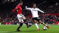 Gelandang Manchester United, Henrikh Mkhitaryan berusaha menghalau bola tendangan pemain Derby County, Marcus Olsson saat bertanding pada babak tiga Piala FA di Old Trafford, Inggris (5/1). MU menang 2-0 atas Derby County. (Martin Rickett/PA via AP)