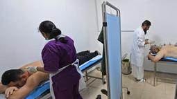 Spesialis melakukan pengobatan hijama atau terapi bekam basah kepada pasien di sebuah klinik di Ajman, Uni Emirat Arab, Kamis (15/8/2019). Hijama berfungsi untuk membuang darah yang telah rusak atau teroksidasi karena tingginya oksidan dalam tubuh. (KARIM SAHIB/AFP)