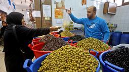 Warga membeli buah zaitun untuk persiapan menyambut datangnya bulan Ramadan di Ibu Kota Tripoli, Libya, 1 Mei 2019. Ramadan kali ini diperkirakan akan terasa berat bagi warga Tripoli karena bayang-bayang krisis dan pertempuran. (MAHMUD TURKIA/AFP)