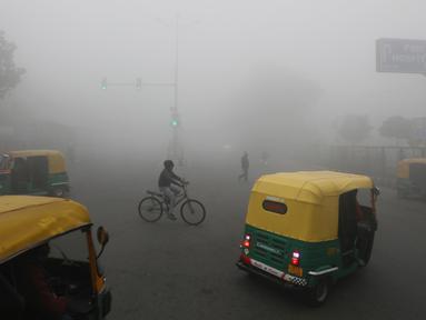 Pengendara sepeda melewati perlintasan di tengah kabut akibat suhu dingin di New Delhi, Senin (30/12/2019). New Delhi, ibu kota India, saat ini mengalami musim dingin dengan hari dingin terpanjang dalam 22 tahun terakhir. (AP Photo/Manish Swarup)