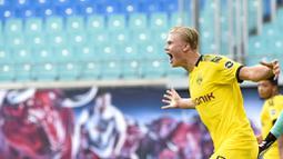 Pemain Borussia Dortmund, Erling Braut Haaland, melakukan selebrasi usai mencetak gol ke gawang RB Leipzig pada laga  Bundesliga di Red Bull Arena Sabtu (20/6/2020). RB Leipzig takluk 0-2 dari Borussia Dortmund. (AP/Jens Meyer)