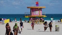 Orang-orang menikmati suasana pantai di Miami, Florida pada Selasa (16/3/2021). Mahasiswa telah tiba di daerah Florida Selatan untuk liburan musim semi tahunan. Para pejabat kota prihatin dengan kerumunan liburan musim semi saat pandemi COVID-19 terus berlanjut. (Joe Raedle/Getty Images/AFP)