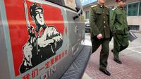 Tentara melewati sebuah stiker yang menampilkan wilayah China bersatu dengan Taiwan (AP Photo)