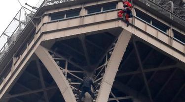 Petugas pemadam kebakaran berusaha mendekati seorang pria (baju hitam di bawah) yang memanjat Menara Eiffel tanpa peralatan keselamatan di Paris, Senin (20/5/2019). Akibat ulahnya, Menara Eiffel ditutup dan pihak pengelola melakukan evakuasi dan pengamanan. (AP/Michel Euler)