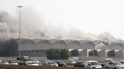 Mobil-mobil melaju saat asap hitam  membumbung menyelimuti gedung Stasiun Kereta Api Cepat Haramain di kota Jeddah, Minggu (29/9/2019). Pasukan Pertahanan Sipil Arab Saudi, dengan dukungan helikopter, harus berjuang selama berjam-jam untuk memadamkan api. (Photo by - / AFP)