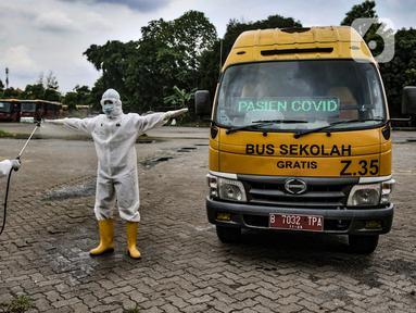 Petugas Kebersihan Bus (PKB) menyemprotkan disinfektan pada sopir bus sekolah saat proses dekontaminasi usai bertugas mengantarkan pasien terpapar Covid-19 di Pool Unit Pelayanan Angkutan Sekolah (UPAS) DKI Jakarta, Kramat Jati, Selasa (5/1/2021). (merdeka.com/Iqbal Nugroho)