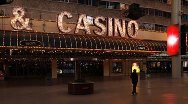 Seseorang berjalan melewati Fremont Street yang sepi setelah perintah penutupan kasino akibat virus corona COVID-19 di Las Vegas, Amerika Serikat, Rabu (18/3/2020). Gubernur Nevada Steve Sisolak menutup sejumlah tempat perjudian di Las Vegas akibat virus corona COVID-19. (AP Photo/John Locher)
