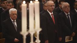 Presiden Palestina Mahmoud Abbas (kiri) menghadiri misa Natal di Gereja Nativity, Bethlehem, Jumat ( 25/12/2015). Abbas selalu mengikuti misa yang dirayakan di tempat yang diyakini banyak orang sebagai tempat lahirnya Yesus. (REUTERS /Fadi Arouri )