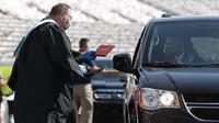 Kepala Sekolah Vance Fishback memberikan ijazah kepada mahasiswa Cabarrus Early College of Technology saat menjalani wisuda di Charlotte Motor Speedway, Concord, North Carolina, Amerika Serikat, Jumat (12/6/2020). Ribuan mahasiswa menjalani wisuda di arena NASCAR. (AP Photo/Gerry Broome)