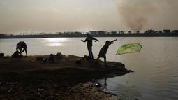 Orang-orang memancing di dasar sungai Paraguay yang terbuka, saat kolom asap membubung di pantai lain, di tengah kekeringan bersejarah yang mempengaruhi ketinggian sungai, di Mariano Roque Alonso, Paraguay, Senin (20/9/2021).  (AP Photo/Jorge Saenz)
