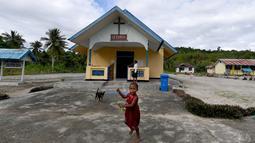 Seorang anak suku Byak Betew bermain di luar gereja pada hari Minggu di pulau Saukabu, satu dari 1.500 pulau di Raja Ampat 20 Agustus 2017. Raja ampat merupakan salah satu habitat laut paling banyak keanekaragaman hayati di bumi. (AFP Photo/Goh Chai Hin)