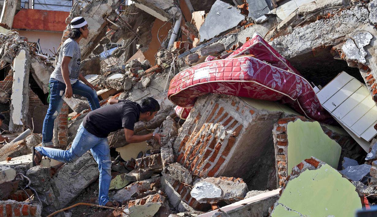 Warga memeriksa bangunan yang runtuh akibat gempa di Mamuju, Sulawesi Barat, Indonesia, Senin (18/1/2021). Hingga Minggu 17 Januari 2021 pukul 20.00 WIB, BNPB melaporkan jumlah korban meninggal akibat gempa Sulawesi Barat menjadi 81 orang. (AP Photo/Yusuf Wahil)
