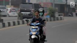 Pengendara motor menembus kabut asap pekat yang menyelimuti Kota Pekanbaru, Riau, Selasa (10/9/2019). Kabut asap akibat kebakaran hutan dan lahan (karhutla) tersebut menurunkan jarak pandang dan kualitas udara turun ke status tidak sehat. (Liputan6.com/Faizal Fanani)