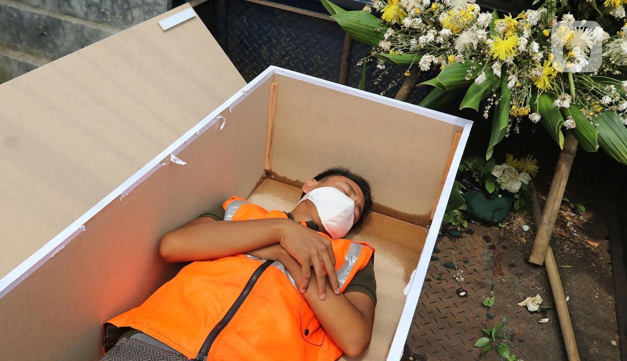 Warga pelanggar PSSB dihukum masuk ke dalam peti mati di Kawasan Kalisari, Pasar Rebo, Jakarta Timur, Kamis (3/9/2020). Warga Kelurahan Pasar Rebo yang tidak menggunakan masker diberikan pilihan hukuman, salah satunya dimasukkan ke dalam peti mati selama 1 menit. (Liputan6.com.Herman Zakharia)