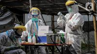 Petugas medis memeriksa sampel saat menggelar swab test COVID-19 di Pasar Tasik, Jakarta, Kamis (2/7/2020). Tes yang dilakukan secara acak bagi pedagang itu bertujuan untuk mendeteksi serta mencegah penyebaran COVID-19 di kawasan Pasar Tasik. (Liputan6.com/Faizal Fanani)
