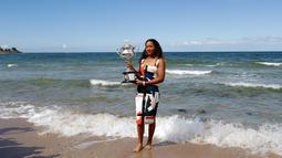 Petenis Jepang, Naomi Osaka menunjukkan trofi juara tunggal putri Australia Terbuka di Pantai Brighton Melbourne, Australia, Minggu (27/1). Prestasi ini membuat Osaka merengkuh gelar Grand Slam secara beruntun. (AP Photo/Kin Cheung)