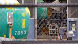 Pekerja Boeing melihat pesawat 737 saat berjalan masuk ke sebuah gedung manufaktur di Renton, Washington, Senin (16/12/2019). Perusahaan pembuat pesawat asal Amerika Serikat (AS) Boeing Co akan menghentikan produksi jet 737 Max di Januari 2020. (AP/Elaine Thompson)